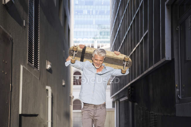 Stylish mature man with longboard walking in alley — Photo de stock