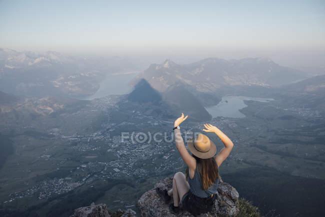 Швейцария, Осер Майтен, молодая женщина, совершающая пешую прогулку, сидящая на скале на рассвете — стоковое фото