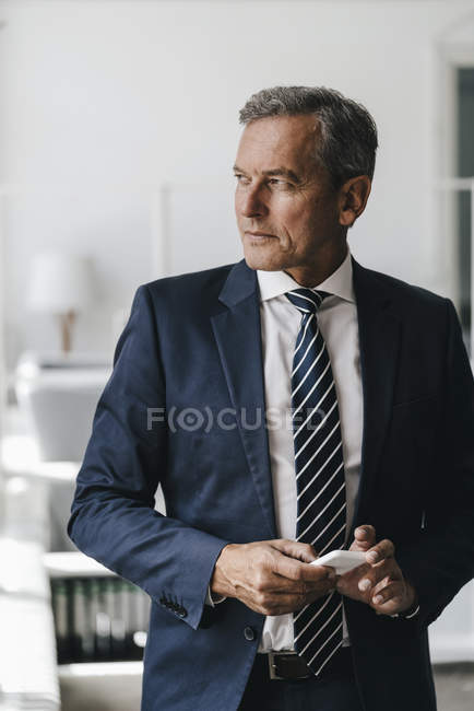 Portrait of mature businessman holding cell phone and looking away in office — Photo de stock