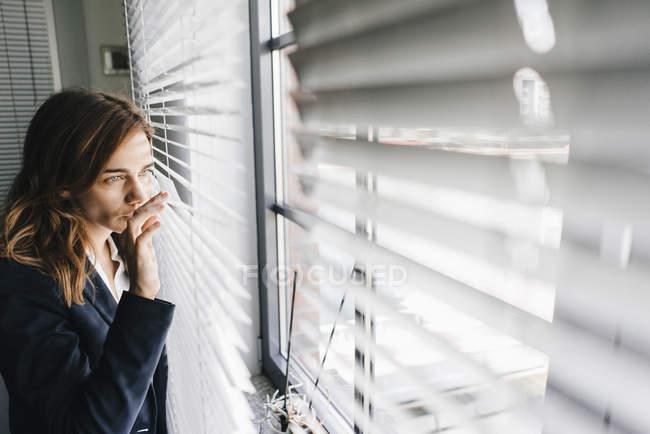 Женщина, стоящая у окна и шпионя через жалюзи — стоковое фото