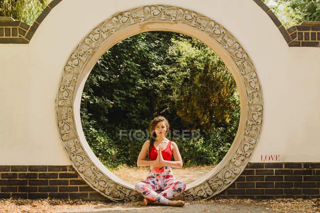 Молодая женщина практикует пилатес в городском парке — стоковое фото