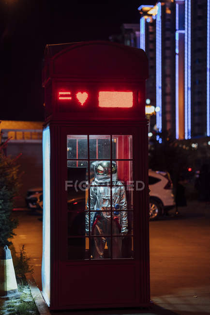 Spaceman standing in telephone box at night — Stock Photo