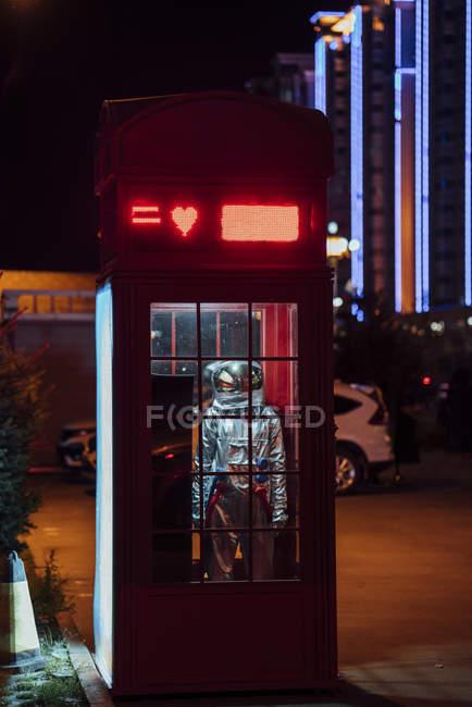 Spaceman de pie en la cabina telefónica por la noche - foto de stock