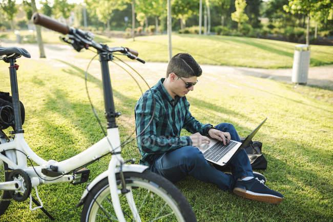 Jeune homme avec vélo utilisant un ordinateur portable dans un parc — Photo de stock