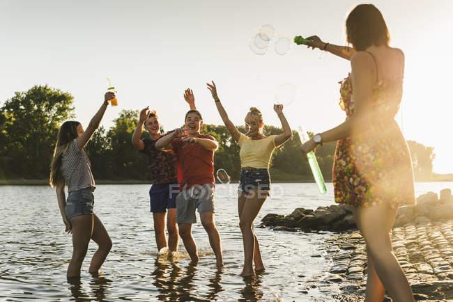 Група щасливих друзів у річці на заході — стокове фото