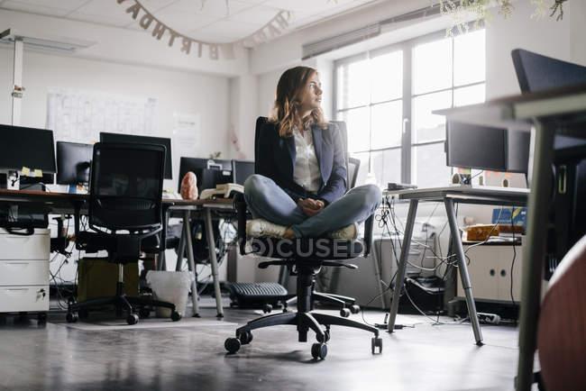 Businesswoman sitting cross-legged on office chair — Stock Photo