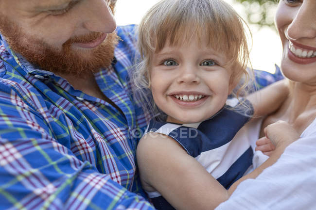 Happy parents hugging her daughter outdoors — Stock Photo