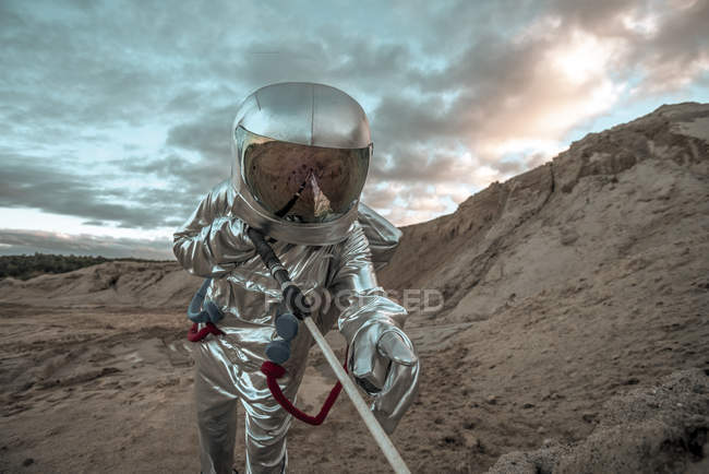 Spaceman on nameless planet, probing soil — Stock Photo