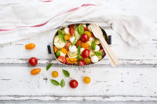 Tortellini salad with tomato, mozzarella and basil in lunch box — Stock Photo