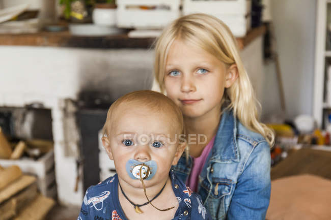 Portrait of girl with baby boy brother at home — Stock Photo