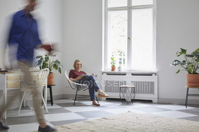 Reife Frau lesen Magazin zu Hause mit Mann vorbei — Stockfoto