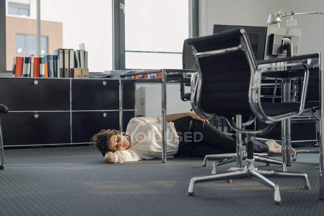 Mulher de negócios tired que dorme no assoalho sua mesa — Fotografia de Stock