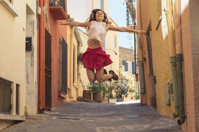 Франція, Коліур, молода жінка стрибає в провулку. — стокове фото