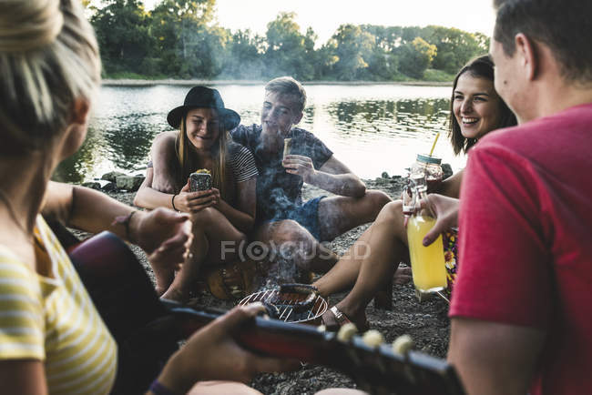 Group of friends sitting together having a barbecue at the riverside — Stock Photo