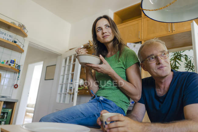 Confident mature couple at home looking sideways and having meal — Stock Photo