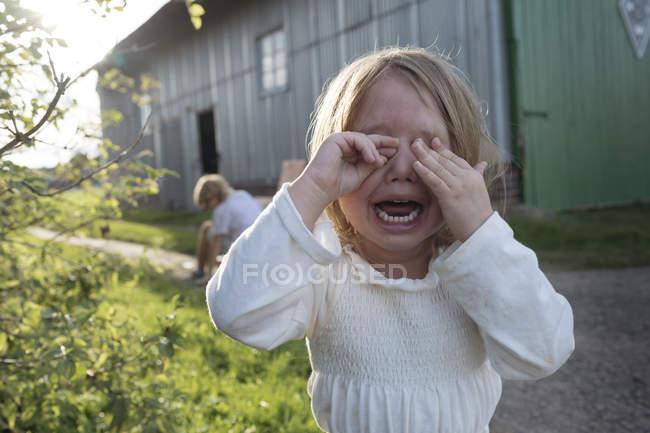 Retrato de gritar menina cobrindo os olhos com as mãos — Fotografia de Stock