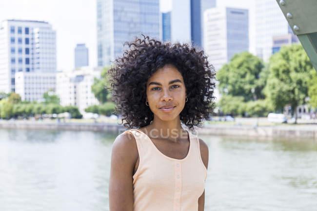 Alemania, Fráncfort, retrato de una joven relajada con el pelo rizado frente al río Main - foto de stock