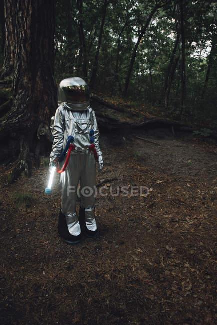Spaceman que explora a natureza, usando a tocha na floresta escura — Fotografia de Stock