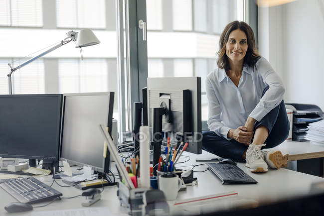 Mature businesswoman sitting on desk in office, smiling and looking at camera — Stock Photo
