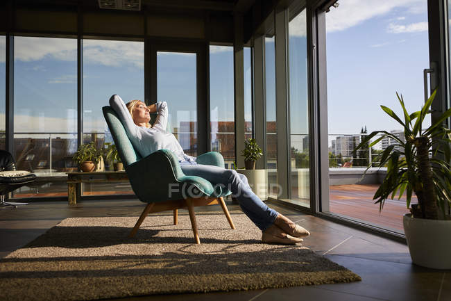 Mature woman relaxing in armchair in sunlight at home — Stock Photo
