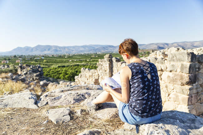 Greece, Peloponnese, Argolis, Tiryns, archaeological site, female tourist reading guide book — Stock Photo