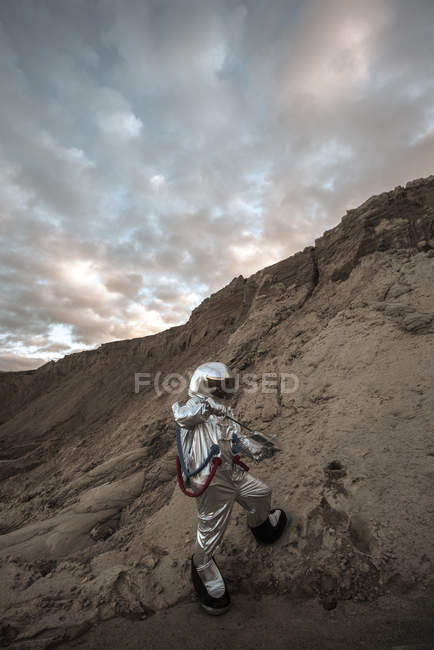 Spaceman on nameless planet taking sample of sand — Stock Photo