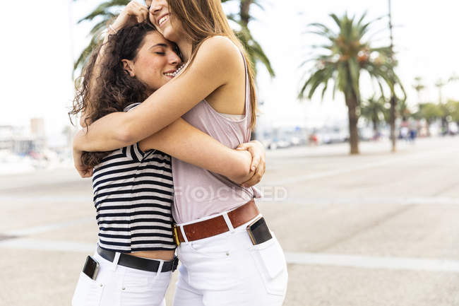Two happy female friends embracing and hugging on promenade with palms — Stock Photo