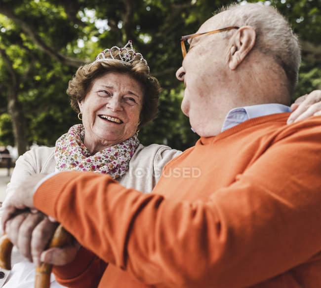 Casal sênior sentado no banco em um parque e falando — Fotografia de Stock