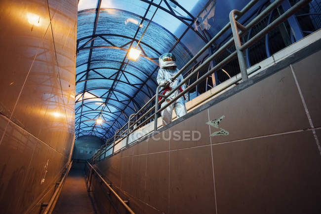 Spaceman in city at night walking in passageway — Stock Photo