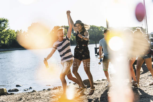 Группа счастливых друзей веселится на берегу реки — стоковое фото