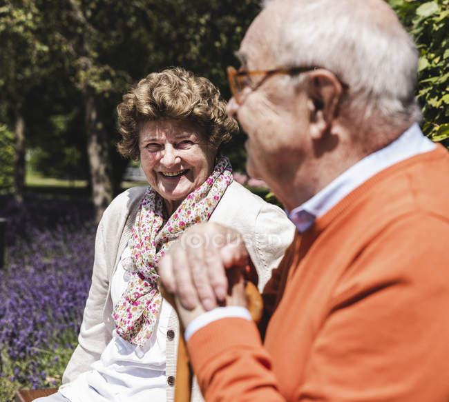 Старший пара сидячи на лавці в парку і говорити — стокове фото
