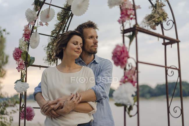 Щасливі пара обіймаючи під весільну арку — стокове фото