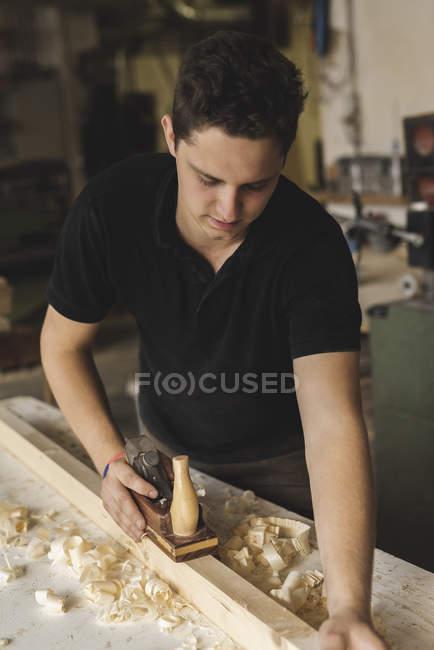 Tischler mit Hobel auf Holzstück in Werkstatt — Stockfoto