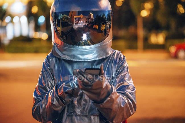 Spaceman en la calle en la ciudad por la noche usando smartphone - foto de stock