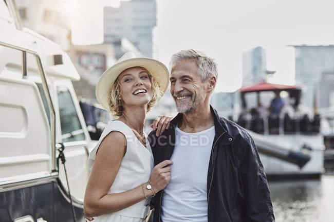 Uomo e giovane donna con differenza di età ridere accanto allo yacht — Foto stock
