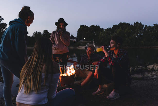 Group of friends at the riverside in the evening — Stock Photo