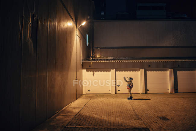 Spaceman standing under lamp at yard at night — Stock Photo