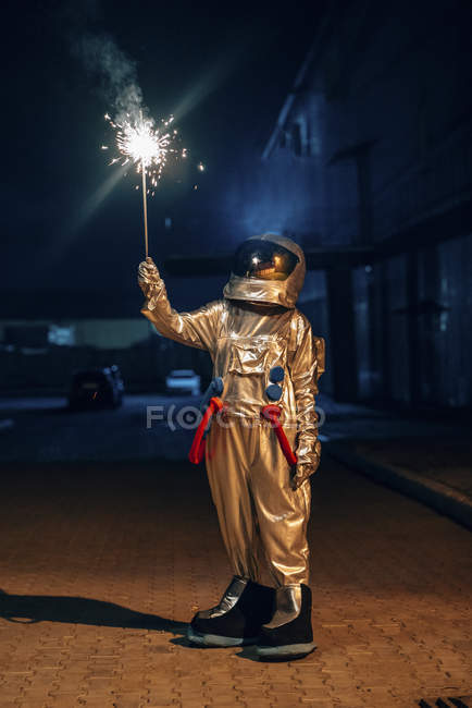 Spaceman standing outdoors at night and holding sparkler — Stock Photo