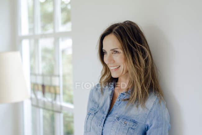 Retrato de mujer madura sonriente en casa apoyada contra una pared - foto de stock