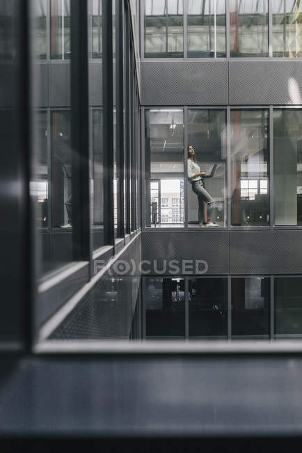 Жінка стоїть на офісному вікні з ноутбуком — стокове фото
