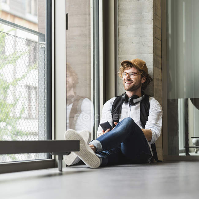 Smiling casual young man with headphones and cell phone sitting at window — Stock Photo