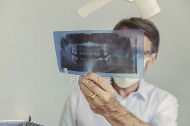 Dentista olhando para a imagem de raios-x antes do tratamento — Fotografia de Stock