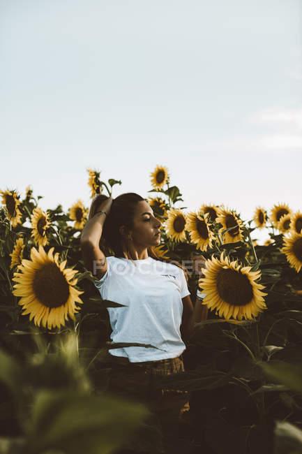 Портрет молодой женщины, стоящей в поле подсолнухов, рука в волосах — стоковое фото