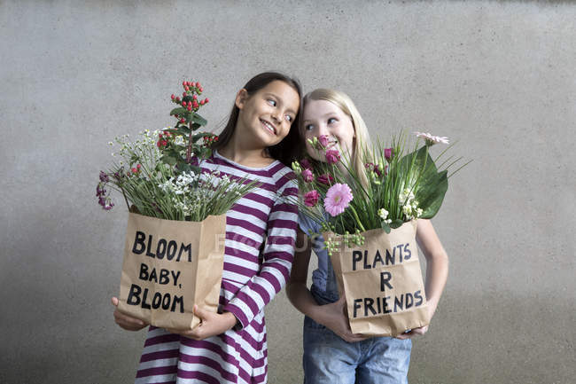Portrait of two smiling girls holding paper bags with flowers — Stock Photo