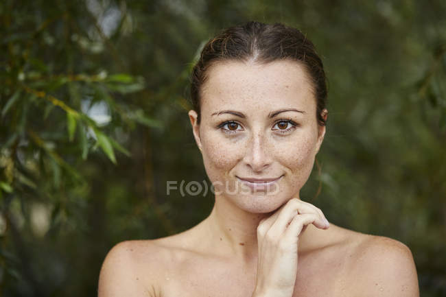 Portrait of freckled young woman in nature — Stock Photo