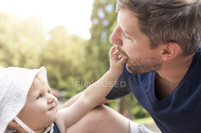 Little girl feeding father with a grape — Stock Photo