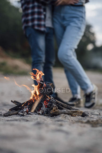Burning campfire at riverside with couple in background — Stock Photo