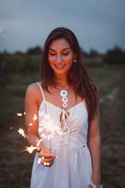 Молодая женщина в природе, горящая искра вечером — стоковое фото