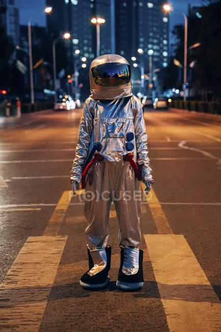 Spaceman de pie en la calle en la ciudad por la noche - foto de stock