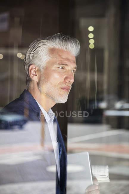 Портрет вдумчивого бизнесмена, выглядывающего в окно — стоковое фото